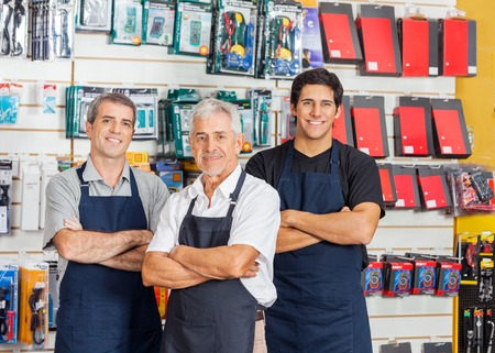 business decisions: Salesmen Standing Arms Crossed In Hardware Shop Stock Photo
