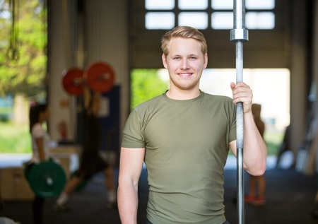 cross bar: Athlete Holding Weightlifting Bar At Gym