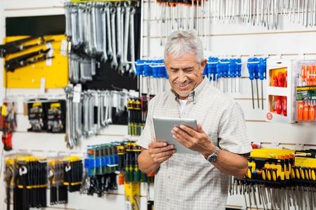 Customer Holding Digital Tablet In Hardware Shop photo