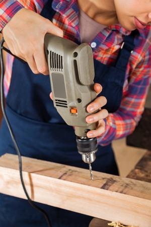 Female Carpenter Drilling Wood In Workshop photo