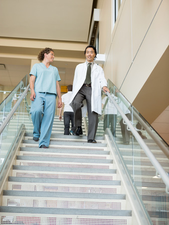 walking down: Low angle view of female nurse and doctor walking down stairs in hospital Stock Photo