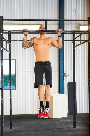 strong chin: Male Athlete Doing Chin-Ups At Healthclub