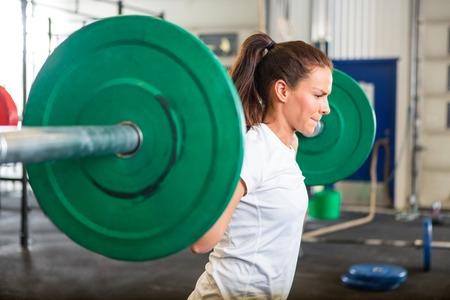 liggande: Fit kvinna lyfta skivstång i gym Stockfoto