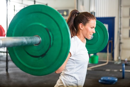 barbell: Fit Woman Lifting Barbell in Gym Stock Photo