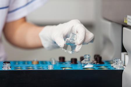 research facility: Cropped image of female researcher loading samples into analyzer Stock Photo