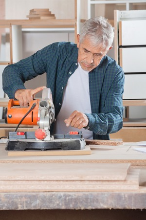 woodworker: Carpenter Using Power Tool On Wood In Workshop Stock Photo