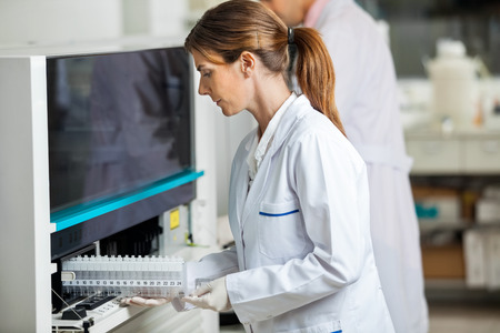 lab tech: Female Researcher Loading Samples In Analyzer