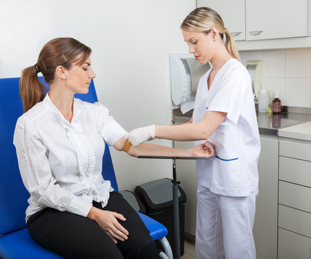 pielęgniarki: Pielęgniarka Przygotowanie Businesswoman Na badanie krwi
