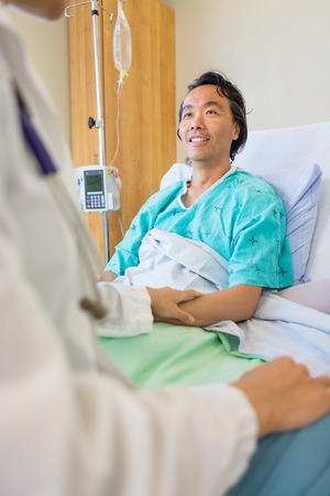 Patient Being Consoled By Doctor On Bed