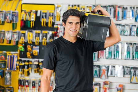 shoulder carrying: Smiling Man Carrying Toolbox On Shoulder In Store Stock Photo