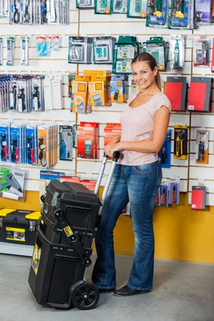 retailer: Woman Holding Tool Case In Hardware Store Stock Photo