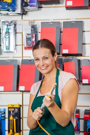 compressed: Saleswoman Holding Air Compressor Hose In Store
