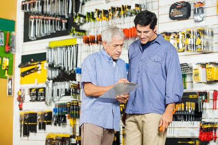 Father And Son Checking Checklist In Hardware Store photo