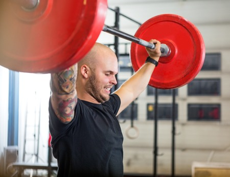 Athlete Exercising With Barbell At Gym 스톡 콘텐츠