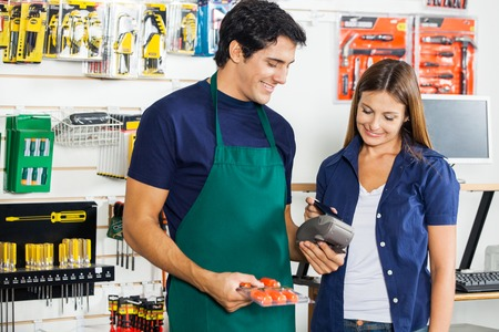 telephone salesman: Worker Accepting Payment From Woman In Hardware Store Stock Photo