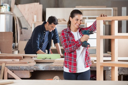 Female Carpenter Drilling Wood In Workshop