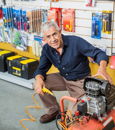 Confident Senior Man With Air Compressor In Store Stock Photo