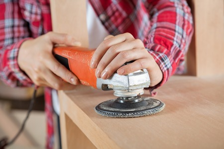 Carpenters Hands Using Sander On Wooden Shelf photo
