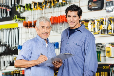 small business owner: Father And Son Preparing Checklist In Hardware Store