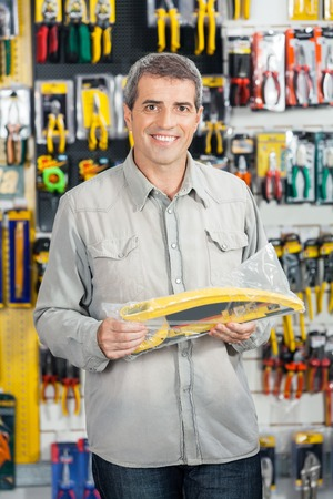 retailer: Portrait of happy mature man buying handsaw in hardware store
