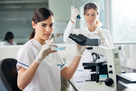 med: Confident Researcher Using Microscope In Lab Stock Photo