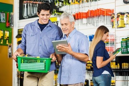 hardware: Padre e hijo que usa la tableta digital en el hardware tienda