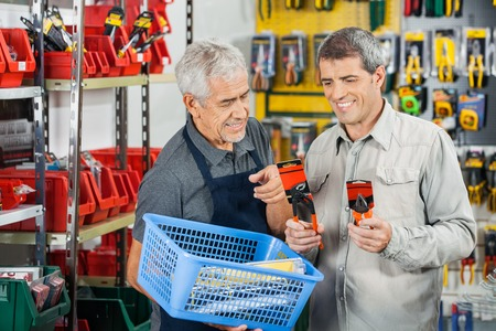 business tool: Salesman Assisting Customer In Buying Pliers Stock Photo