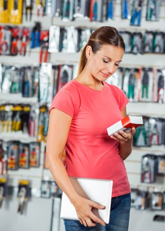 Woman Examining Product In Hardware Store photo