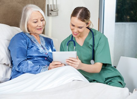 home nursing: Nurse And Senior Woman Using Tablet PC In Bedroom Stock Photo