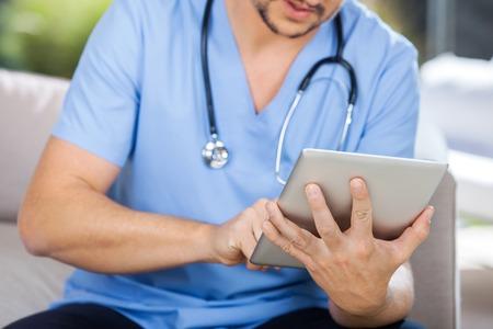 enfermeros: Portero Hombre que usa la tablilla del ordenador mientras que se sienta en el sofá