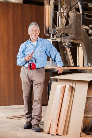 protectors: Senior Carpenter Holding Ear Protectors By Bandsaw