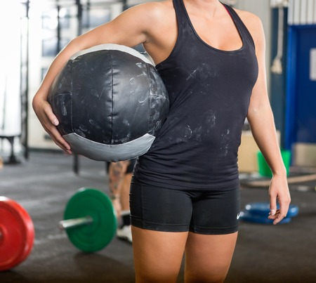 Fit Woman Carrying Medicine Ball