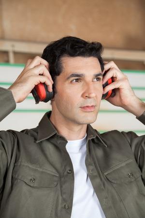 protectors: Thoughtful Carpenter Wearing Ear Protectors