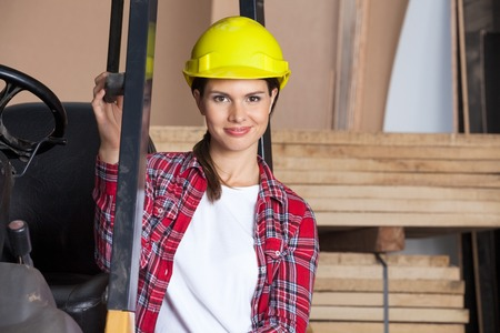 Confident Female Engineer Wearing Hardhat By Forklift photo