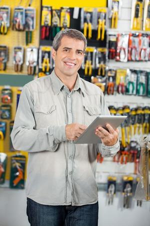 Man Using tavoletta digitale in negozio di ferramenta Archivio Fotografico
