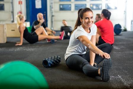 fitness men: Mujer que hace ejercicio del estiramiento en la caja de Formaci�n de la Cruz