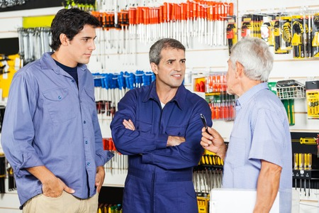 Worker Communicating With Customers In Hardware Shop photo