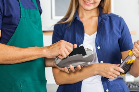 retailer: Worker Swiping Credit Card With Woman Holding Screwdriver Set