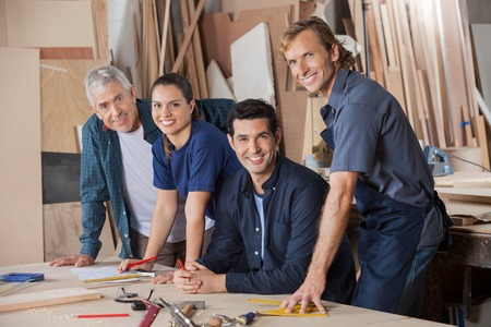 Confident Carpenters Working At Workshop Table photo