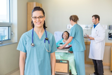 Nurse Smiling With Patient And Medical Team In Background Stock Photo