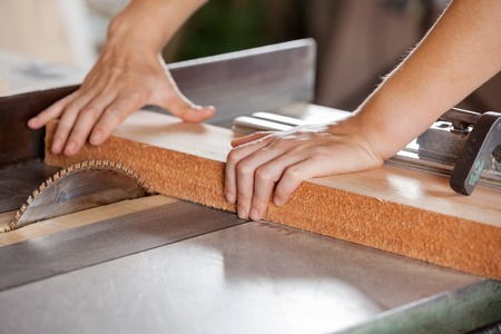 Carpenters Hands Cutting Wood With Tablesaw photo