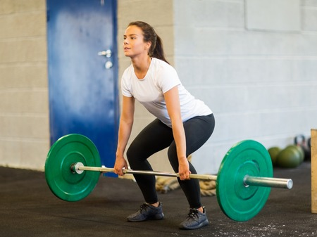 weightlifting equipment: Woman Lifting Barbell Stock Photo