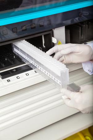 analyzer: Researcher Loading Samples In Analyzer Stock Photo