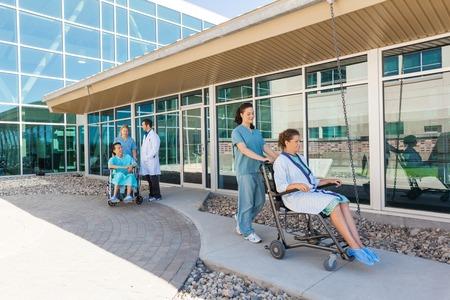 병원 마당에서 휠체어에 환자와 의료 팀