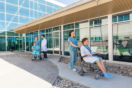 empujando: Equipo médico con los pacientes en sillas de ruedas en el Hospital Patio Foto de archivo