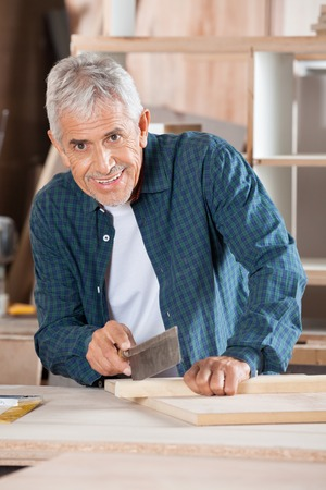 handsaw: Portrait of senior man cutting wood with small saw at table in workshop Stock Photo