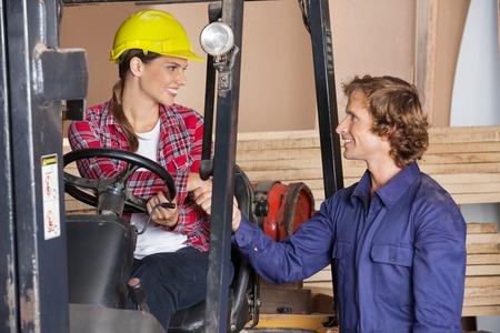 Supervisor In Forklift Shaking Hands With Carpenter photo
