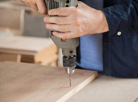 taladro: Carpintero que usa el taladro en la madera en el taller Foto de archivo