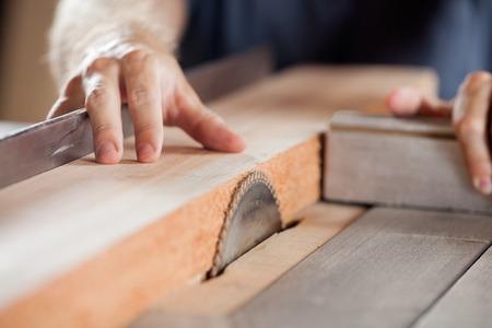 carpintero: Carpinteros Manos de cortar madera con tablesaw Foto de archivo
