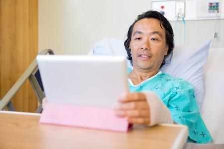 paciente en camilla: Paciente que usa la tablilla digital mientras recostado en la cama de hospital